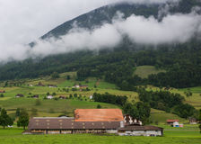Farmland with house and animals. Farmland in Europe with houses and low clouds on the mountains Stock Photography