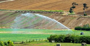 Water cannons used for irrigation. Farmland in rural New Zealand uses irrigation extensively. Here the simple water cannon is used to water vast tracts of stock image