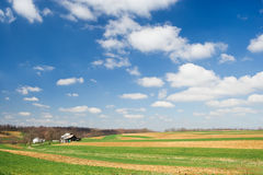 Farmland And Sky. Idyllic rural scene of wide open cultivated farmland and an old barn with a deep blue sky and cottony clouds royalty free stock photos