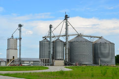 Farmland with Steel Grain Industrial Silo Towers. Steel grain industrial silo containers with tall towers with a cloudy blue sky in the background royalty free stock photography