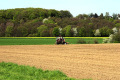 Farmland with tractor in germany. Farmland in germany with tractor and forest in background Royalty Free Stock Image