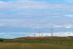 Farmland with view of huge wind turbines windmill in background, Stock Photography