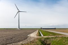 Farmland with a wind turbine of the biggest windfarm in the Netherlands Royalty Free Stock Photo