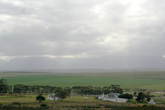 Farmlands. Wide shot of a typical southern-coast South African farmland with green wheat fields and old farm buildings Stock Photography