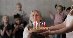 Farmodern blåser ut stearinljus på födelsedagkakan lager videofilmer