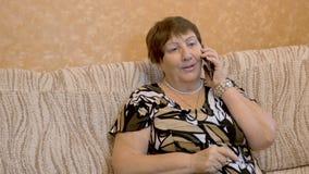 Farmodern den gamla kvinnan använder upp Smartphone, slut lager videofilmer