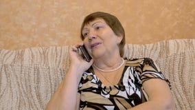Farmodern den gamla kvinnan använder upp Smartphone, slut stock video