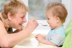 Farmodern ger sig behandla som ett barn mat från en sked Arkivfoto