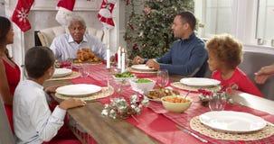 Farmodern kommer med ut julkalkon till familjen som placeras runt om tabellen för lunch som alla applåderar, som farfadern förber stock video