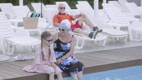 Farmodern kramar hennes sondotter som sitter vid pölen och blicken på kameran Farfadern vilar att ligga på sunbed arkivfilmer