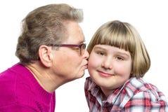 Farmodern kysser barnbarnet på kind Arkivbilder