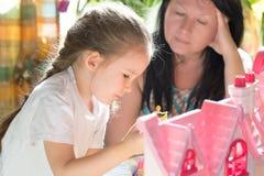 Farmodern med den gulliga lilla flickan spelar hemma bolts muttrar för sammansättningsbegreppsfamilj Royaltyfri Fotografi