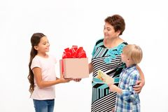 Farmodern och hennes barnbarn som utbyter gåvor royaltyfri foto