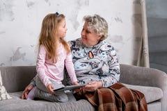 Farmodern och hennes lilla sondotter h?ller ?gonen p? filmer tillsammans och spelar p? apparaten, medan sitta p? soffan arkivbild