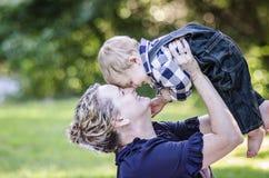 Farmodern och lyckligt behandla som ett barn arkivbild