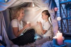 Farmodern och sondottern äter kakor med mjölkar i filthus på natten hemma fotografering för bildbyråer