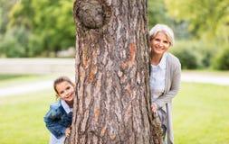 Farmodern och sondottern bak träd på parkerar royaltyfria foton
