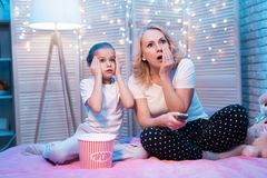 Farmodern och sondottern håller ögonen på film på tv på natten hemma arkivbilder