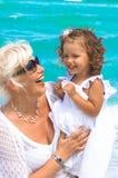 Farmodern och sondottern har gyckel på stranden Arkivfoton