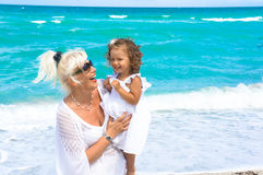 Farmodern och sondottern har gyckel på stranden Fotografering för Bildbyråer