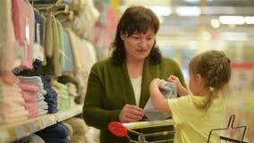 Farmodern och sondottern köper objekt på shoppinggallerian Sondottern sitter i shoppingspårvagnar lager videofilmer