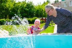 Farmodern och sondottern nära springbrunnen hällde in i en bu arkivbilder