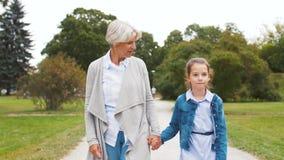 Farmodern och sondottern som går på, parkerar stock video