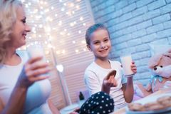 Farmodern och sondottern tycker om mjölkar och kakor på natten hemma royaltyfri bild