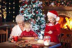 Farmodern och ungar bakar julkakor Arkivfoto