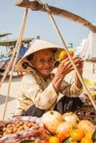 Farmor en försäljare av fruktsammanträde nära korgen Arkivfoto