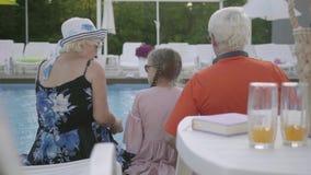 Farmor-, farfar- och barnbarnmotsats som sitter på kanten av den lyxiga pölen Lycklig v?nlig familj Vila in stock video