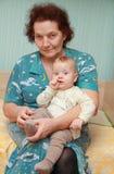 Farmor med hennes sonson på säng arkivfoto