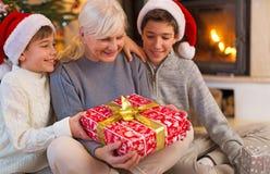 Farmor med hennes två barnbarn som rymmer en julgåva royaltyfri fotografi