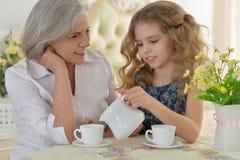 Farmor med lilla flickan som dricker te Arkivbild