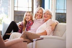 Farmor med moder- och vuxen människadottern som kopplar av på soffan Arkivbilder