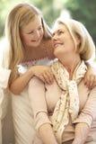 Farmor med sondottern som tillsammans skrattar på soffan Arkivfoto
