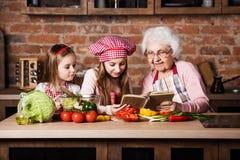 Farmor med två sondöttrar som läser recept royaltyfria foton