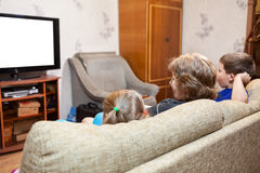 Farmor med två unga ungar som hemma sitter på soffan och hållande ögonen på tv, isolerad vit skärm royaltyfri foto