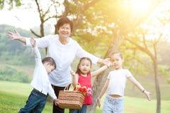 Farmor och barnbarn som har gyckel på utomhus- Arkivbild
