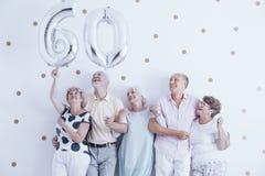 Farmor och farfar med silverballonger som firar 60t Arkivbild