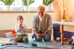 Farmor och liten sonson som spelar med tävlings- bilar Royaltyfria Bilder