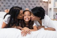 Farmor och moder som kysser le flickan, medan ligga på säng Fotografering för Bildbyråer