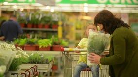 Farmor och sondotter på shoppinggallerian De har mycket gyckel som sniffar blommor stock video