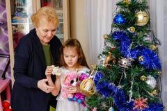 Farmor och sondotter som dekorerar en julgran arkivfoto