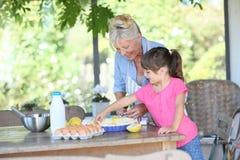 Farmor och sondotter som gör en äppelpaj royaltyfri foto