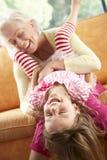 Farmor och sondotter som har gyckel på soffan Royaltyfri Fotografi