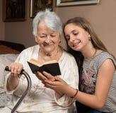 Farmor och sondotter som läser en bok Royaltyfri Bild