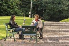 Farmor och sondotter som pratar på trädgården arkivfoto