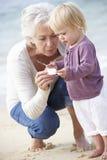 Farmor och sondotter som ser Shell On Beach Together Royaltyfri Bild