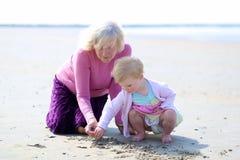 Farmor och sondotter som tillsammans spelar på stranden Arkivfoto